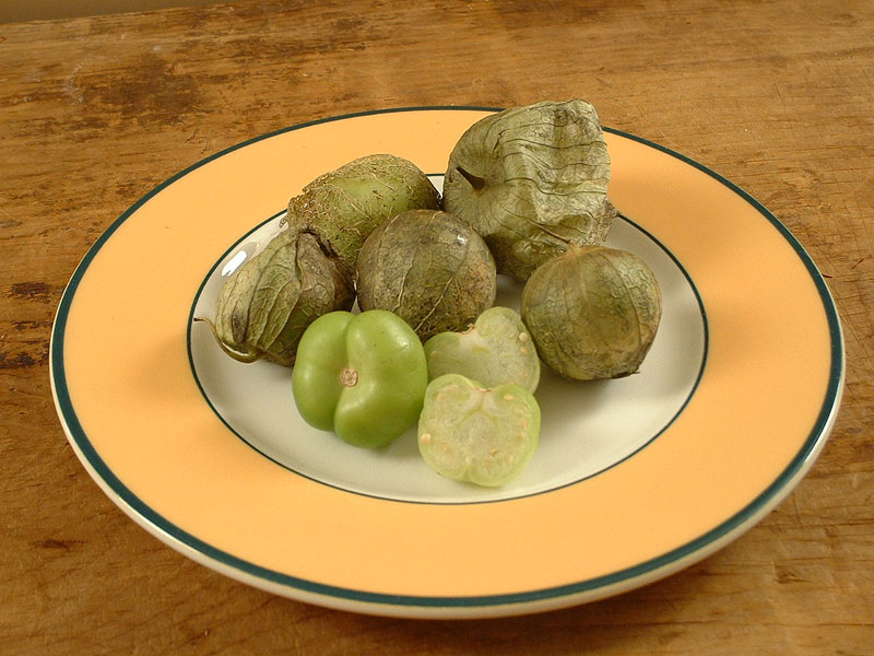 Tomatillos. Showing unhusked, husked, and husked and cut in half